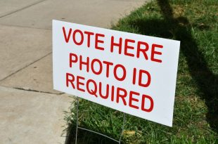 Sign showing where to vote on election day at the polling place. Vote Here, Photo ID Required