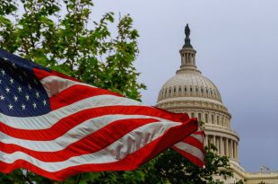 The US Capitol building with a waving American flag superimposed on the sky Capitol Hill in