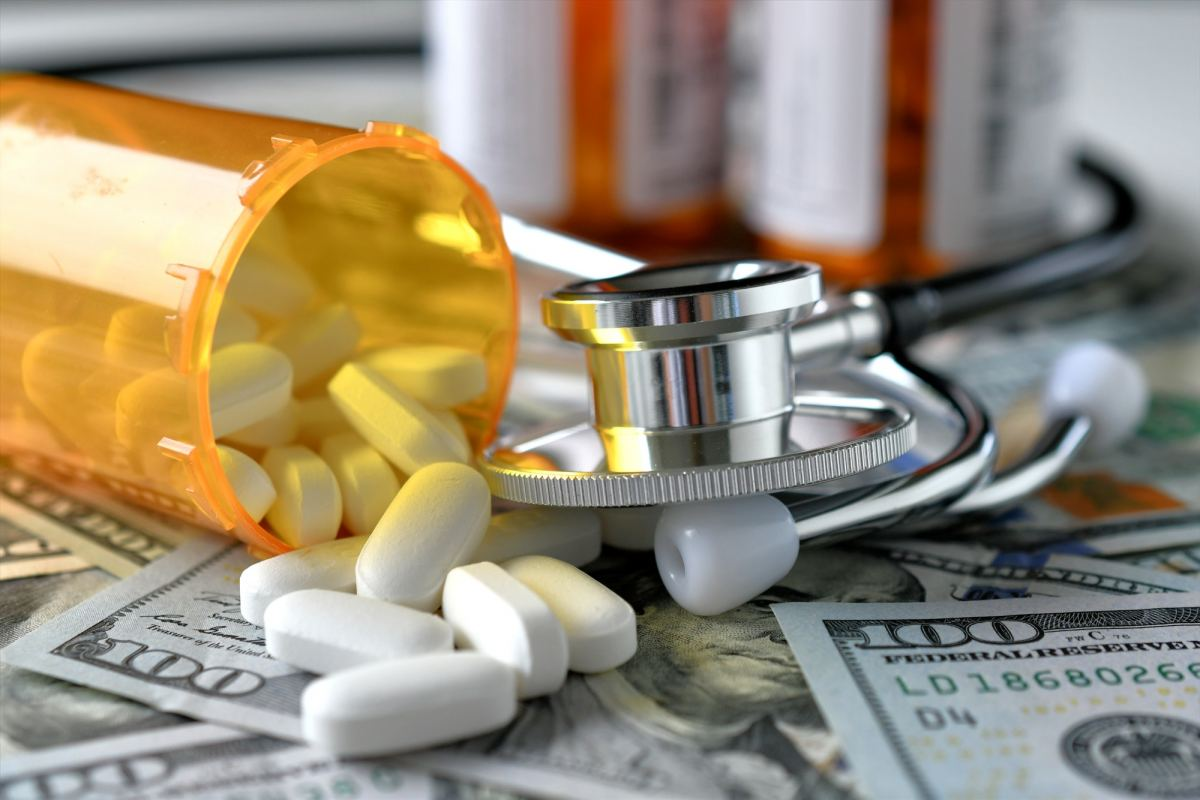 A stethoscope laying on medicine white pills and money with an RX prescription drug bottles